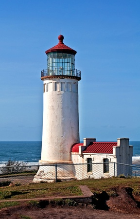 This is the North Head lighthouse off the Pacific ocean in Washington state in Pacific County, with a bright clear blue sky.  Beautiful lantern room is at the top with a red roof for details.  North Head is one of the windiest places in the United States.