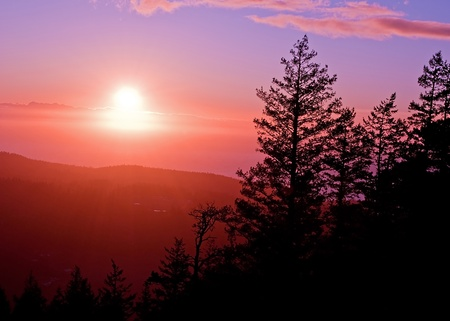 valley below: This is a sunset photo taken off the top of Mt Erie that is stunning and shows some hazy clouds settling at the tops of the mountains and valley below. Stock Photo