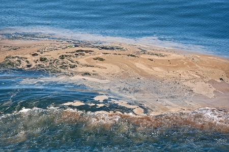 This horizontal image is an environmental shot of ocean water with pollution and an oil spill in the wake of a surf