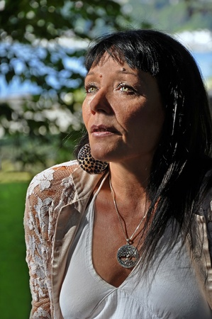 This portrait is an older Native American woman with striking green eyes and long black hair, outdoors.  It is a waist up image with a side view in vertical orientation. photo