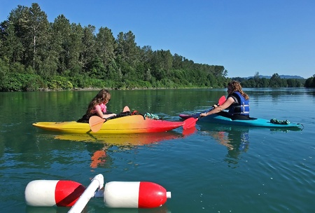 This young mother and daughter are resting while kayaking each in their boats, along a slow, lazy river, enjoying the outdoor recreational sport. photo