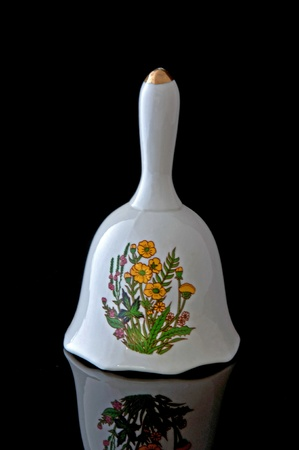 home related: This stock image contains a glass white bell with yellow flowers on the design front.  This home related decor object is isolated on a black background, with reflection on the front. Stock Photo