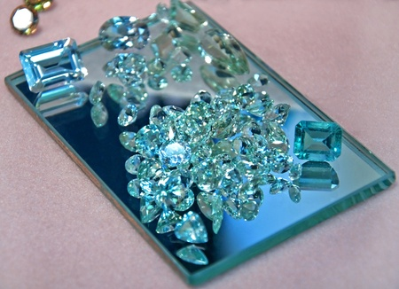 beryl: This stock image shows loose aquamarine gemstones in both cut rectangular shapes and round diamond cut shapes on a rectangle mirror, full of sparkle and shine. Stock Photo
