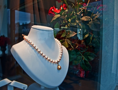 This is a pearl drop necklace store display with red roses with dramatic lighting for a romantic gift idea, especially for Valentine photo