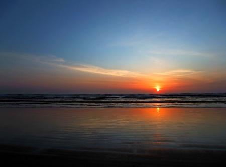 getaways: Esta foto de archivo es una impresionante puesta de sol en la playa mientras el sol est� a punto de sumergirse en el horizonte. Formato horizontal esto transmite los conceptos de vacaciones, escapadas, paz, tranquilidad, descanso, tranquilidad. Foto de archivo