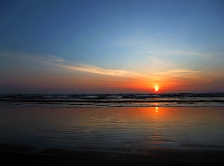 conveys: This stock photo is a stunning sunset at the beach as the sun is just about to dip over the horizon.  Horizontal format this conveys of concepts of vacation, getaways, peace, tranquility, rest, quiet.