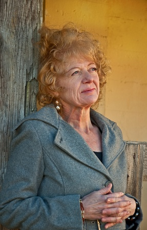 This Caucasian woman is in a thoughtful pose, wearing professional clothing in a rustic setting.  She has strawberry blond hair and is in her fifties.  Vertical and wearing a gray blazer. photo
