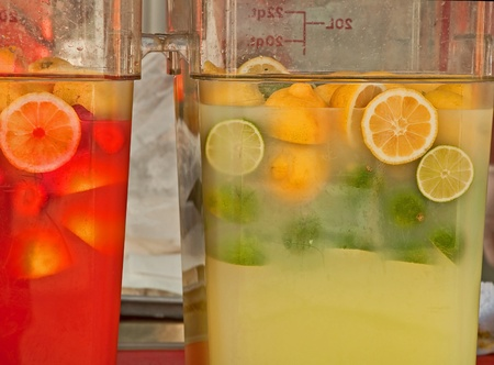 Two large containers of lemonade, limeaid and punch, with citrus slices floating in the icy beverages.  Cool, and inviting.