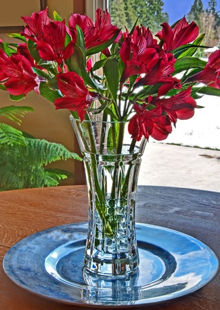 This vertical stock image is a bouquet of red lily flowers in a crystal vase of vase.  Outside the glass door is a snowy winter day.