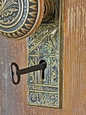 antique keyhole: This is a retro, metal intricate design doorknob, with the metal key in the keyhole to unlock the wooden door.  Vertical antique image with many conceptual ideas. Stock Photo