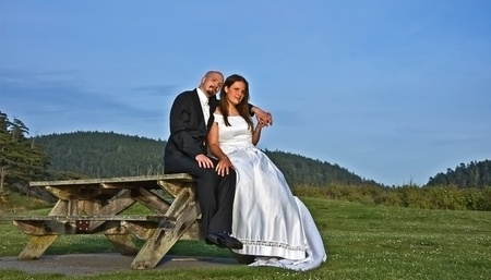 This young Caucasian bride and groom are sitting outdoors on a rustic picnic table with the groom photo