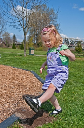This Caucasian 3 year old toddler girl is stomping dirt in her black Mary Jane shoes outdoors in a park.  She