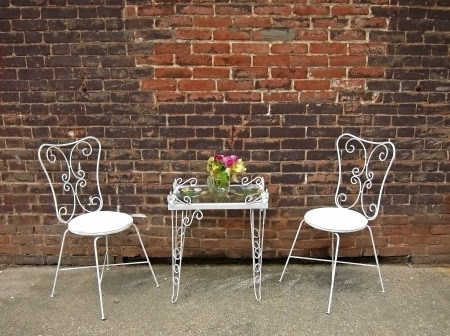 flower arrangement white table: This still life is a white table and chairs decorated with painted plates and flowers, against a rustic brick wall