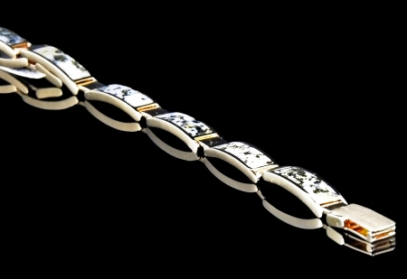 This fine gold jewelry is Black Hills gold flakes sectioned on a bracelet placed in a diagonal pattern on a black background   Plenty of room for text