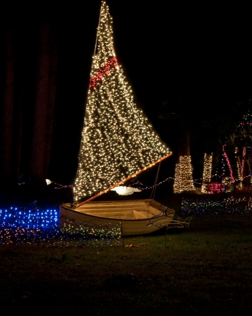 christmas lights display: This vertical holiday image is a sailboat with Christmas lights at night for a holiday display