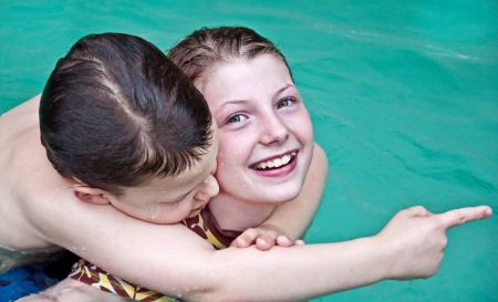 This elementary aged boy and girl are swimming and playing in a pool   The pool has piggy backed on the girl and is pointing at something in the distance Stock Photo - 13830041