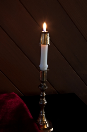 taper: This is a white taper candle, lit on a gold candleholder base with dark wood background and red fabric next to it in a vertical orientation