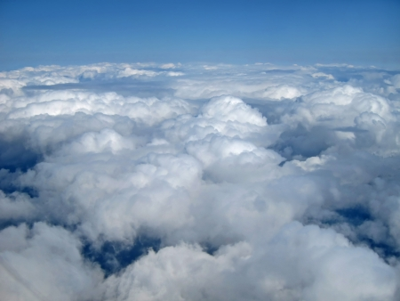 This stock image is of white, puffy clouds and blue sky above the clouds, from a mid air perspective  Stock Photo