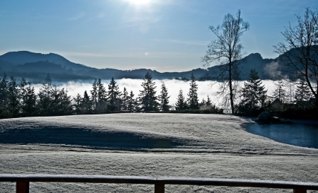 This landscape is a frosty winter morning with heavy fog coming up over a valley, the grass is white with frost   The pond is frozen over and otherwise a clear, cold, crisp day   Plenty of evergreen trees add to the beauty  photo