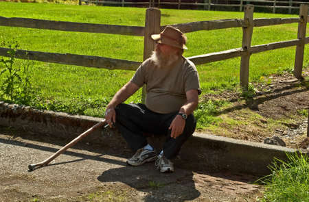 This older rustic looking man with a long beard is sitting down with his cane, and taking a smoke break in a rural farm setting  photo