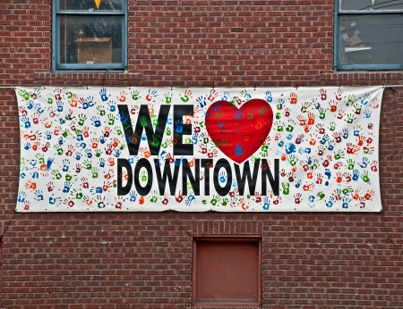 handprints: This sign with handprints all over says We Love Downtown with a heart for the word love   It
