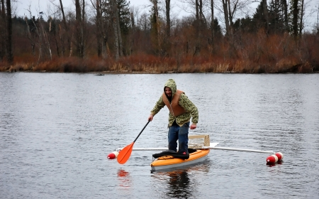 This young man is standing in a canoe that has outriggers on it, trying to tip it over.  He's wearing a lifevest, and camoflauge sweatshirt in cold weather. photo