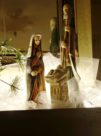 This is the Holy family nativity Christmas scene decor in dramatic lighting   White sheer fabric surrounds them against a mirror backdrop and taken with decor lights in a darkened room   Very pretty holiday vertical image  Stock Photo - 14443269