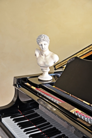 This classic musical still life has a portion of a black grand piano with an art bust sitting on the instrument with plenty of room for text on the blank wall above