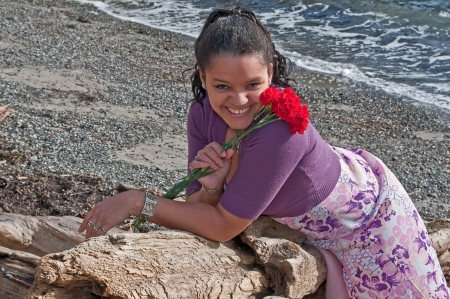 This pretty multi-racial woman in her thirties is smiling and happy on the beach   She is holding some red carnations and laying on her stomach on some driftwood and wearing a floral pastel colored dress  photo