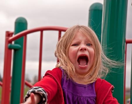 Esta muy enojado ni�a de 4 a�os de edad preescolar est� jugando en un patio de recreo