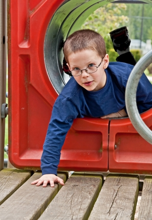 This cute 8 year old Caucasian boy is playing on playground equipment in a tunnel     photo