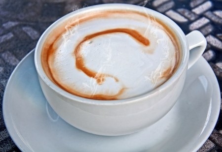 dribbled: This closeup of a white cup and saucer with coffee latte has the letter C dribbled in the foam for a type of coffee art   Piping hot steam is coming off the beverage