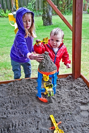 2 5 months: These siblings, a brother and sister and playing in a sandbox outdoors on a cold, wet day   Both are bi-racial, one is 18 months old, the other 4 years old   Classic childhood family time