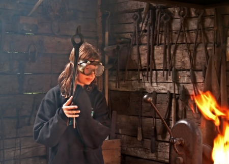 safety googles: This young modern girl has safety googles on while trying to learn blacksmith skills, with old pioneer tools and a live fire.