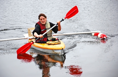 This young adult Caucasian woman is kayaking in colder weather   She is using a boat with homemade outriggers to help stablize her outdoor recreation Stock Photo - 15005652