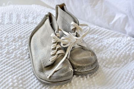 This is a pair of old vintage white baby shoes on a white old fashioned bedspread   These were typically known as baby