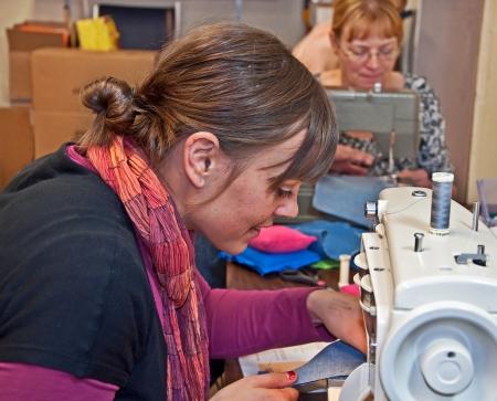 Estas dos mujeres cauc�sicas est� cosiendo en las m�quinas de coser, una es de mediana edad, y el otro es un aprendizaje de los adultos j�venes c�mo Foto de archivo