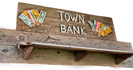 fake money: This rustic old west style sign has town bank on it, with a wooden shelf, and fake money, isolated on a white background.  Horizontal format.