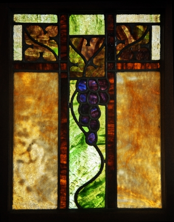 stained glass panel: This vertical image is a stained glass window with neutral brown and tan colors with a cluster of grapes within its panel