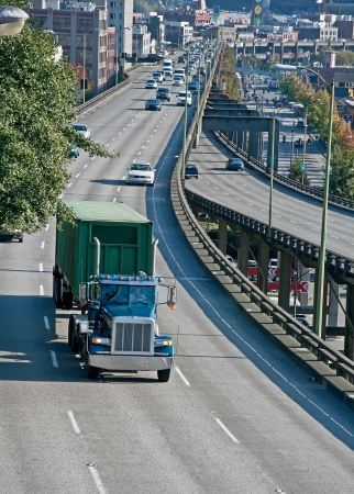 hauling: This is a big rig truck hauling a load on a busy freeway in an American city   Daytime the road is on a slight curve in a vertical format