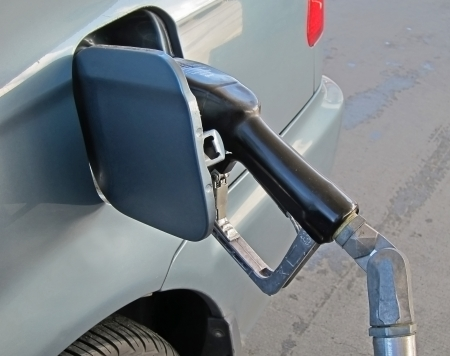 fueled: This light blue car is getting fueled at a gas station with the gas nozzle in the gas tank