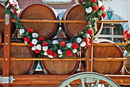 kegs: barrels or kegs of beer in a cart, draped with a garland of flowers for a celebration Stock Photo