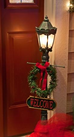 welcome sign: Cette maison porte Sc�ne de No�l est un lampadaire ext�rieur traditionnel avec un signe de bienvenue et une couronne Banque d'images