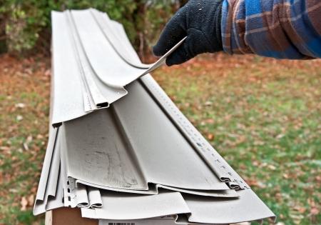 이 낀된 손 바닥에 비닐 사이 딩의 스택에서 비닐 사이 딩의 조각을 리프팅입니다 주택 개선을위한 몇 가지 재료를 검사 스톡 콘텐츠