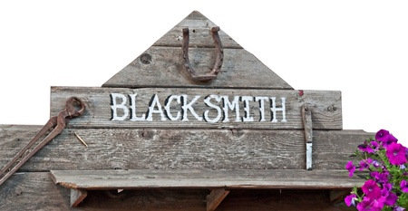 This is an old sign with word blacksmith on rustic wood boards and rusty old vintage tools   Purple petunia flowers add a splash of color   Isolated on a white background