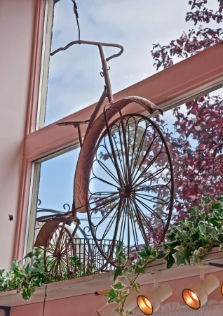 This is a vintage, wrought iron in pink tones inside a window with blue sky and trees outdoors  Banco de Imagens