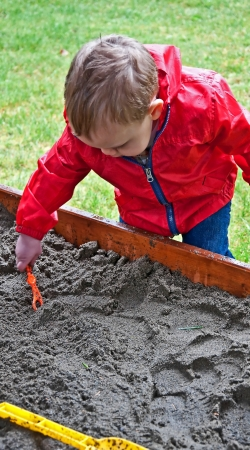 18 month old: This 18 month old toddler boy is playing in a sandbox and digging in the sand on a rainy day   He is wearing his red raincoat