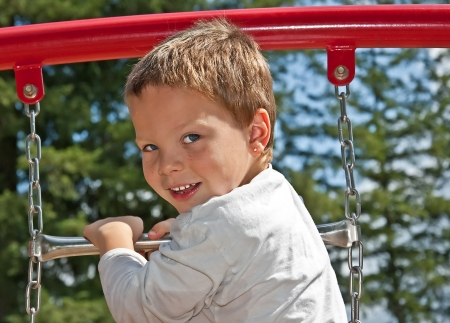 This cute 4 year old Caucasian boy with blue eyes and freckles in playing on some playground equipment outdoors   He photo