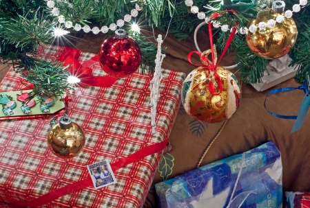 beautifully wrapped: This is some beautifully wrapped Christmas gifts closeup, under a decorated and lit Christmas tree, for a horizontal holiday image  Stock Photo