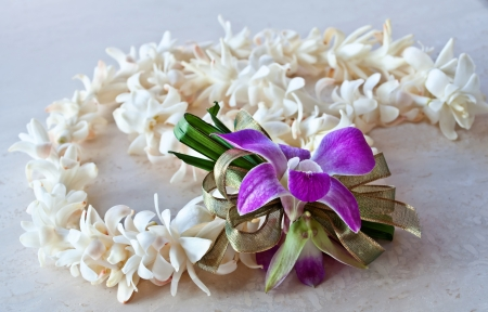 This tropical still life is a Hawaii Lei made of white tuberose flowers, a purple orchid and ribbon   It is lying on a light surface